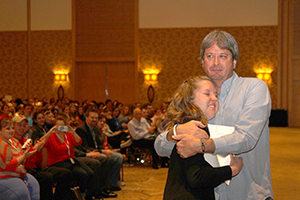 Taylor R. Blatchford of Mountain Vista High School, Highlands Ranch, Colo., embraces her adviser, Mark Newton, MJE, after being named the 2014 National High School Journalist of the Year.